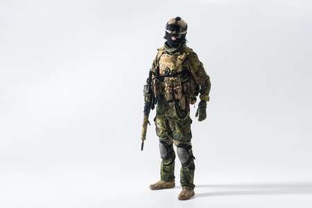 Full length portrait of orderly defender keeping assault rifle in arms. War and peace concept
