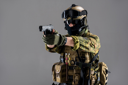 Portrait of serene soldier pointing pistol while wearing in ammunition. Military concept. Isolated