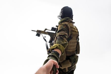 Defender keeping man by hand while turning back to camera. Military and help concept. Isolated Stock Photo