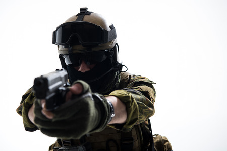 Portrait of strong soldier in balaclava and helmet shooting with pistol. Profession concept. Isolated