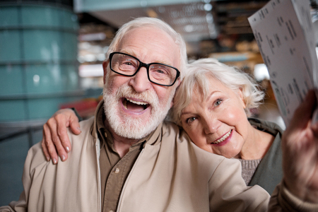 Happy journey. Portrait of delighted old romantic couple is standing at modern terminal. They are looking at camera with joy. Old man is holding his tickets while senior woman is hugging him