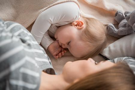 Mütterliche Wärme. Draufsicht des schlafenden Babys Pause mit Mama auf dem Bett machend und säubernd besitzen Daumen