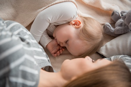 Maternal warmth. Top view of sleeping baby taking rest with mommy on bed and suckling own thumb Stock Photo