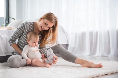 Integrale della madre sorridente che si siede sul tappeto molle e che mostra all'orsacchiotto a sua figlia adorabile Archivio Fotografico - 92592069