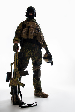 Full length low angle portrait of serene soldier keeping modern weapon near leg. Army concept Stock Photo