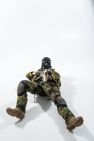 Full length portrait of grave defender lying on floor while shooting with assault rifle. Protection concept. Copy space