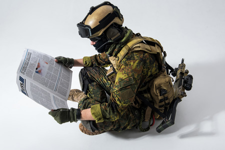 Side view calm defender in army ammunition reading newspaper while situating on floor. Mass media and war concept