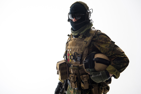 Portrait of serious soldier speaking by digital device while holding helmet in hand. Protection and conversation concept. Isolated and copy space