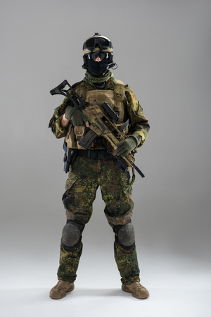 Full length portrait of stern soldier keeping assault rifle in hand. Army concept Banco de Imagens - 92592153
