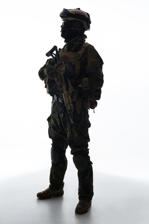 Full length side view serene soldier serving with assault rifle. Military concept