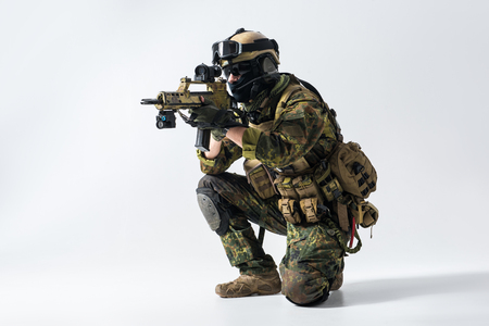 Portrait of orderly soldier looking at sniper scope of modern assault rifle. War concept