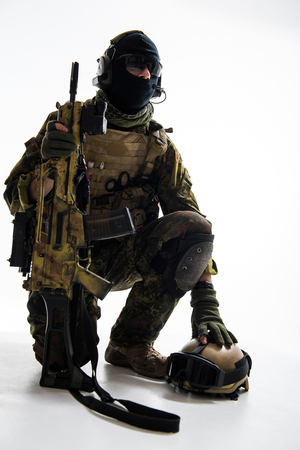 Portrait of calm peacemaker kneeling while holding assault rifle. Protection concept Stock Photo