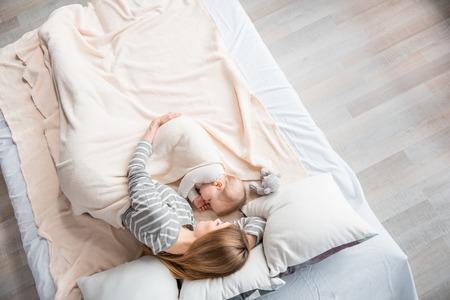 Widok z góry młodej kobiety relaks z dzieckiem w uścisku. Dziecko trzyma palec w ustach Zdjęcie Seryjne