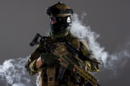 Side view stern soldier wearing military ammunition while keeping assault rifle in rms. He standing in smoke. Protection concept