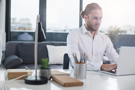 Time to work. Waist up portrait of serious businessman concentrated on laptop screen. He is typing. Copy space in left side