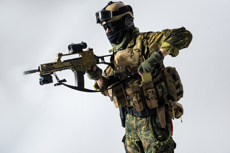 Side view severer peacemaker shooting assault rifle while taking machine gun clip from pocket. Military concept. Isolated