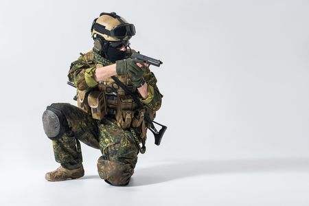 Portrait of serious defender kneeling while shooting with gun. Protection and attack concept. Copy space