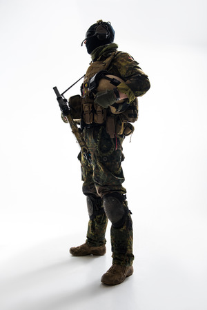 Full length side view grave defender telling by gadget while holding assault rifle in hands. Military concept Stock Photo