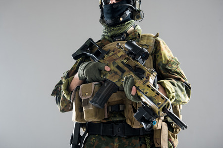 Close up soldier arms holding weapon. He wearing modern body armour. War concept. Low angle and isolated