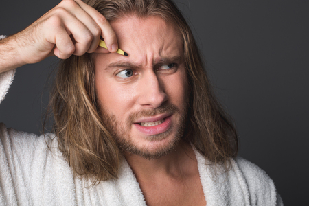 Portrait of displeased man plucking eyebrows, his forehead wrinkled in pain. Isolated on grey background Stock Photo