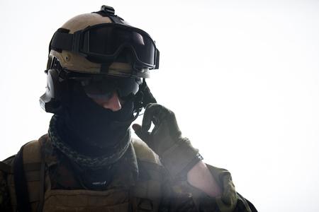 ポータブルラジオセットで話す穏やかなディフェンダーの肖像。陸軍とコミュニケーションの概念。分離スペースとコピースペース