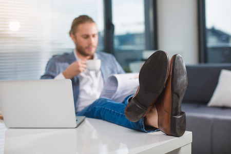 Nothing to do. Relaxed office employee braking off in the office. He is holding magazine and hot drink. Focus on man legs laying on the table near laptop Stock Photo