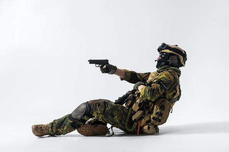 Full length side view orderly defender shooting with gun while lying on ground. War concept