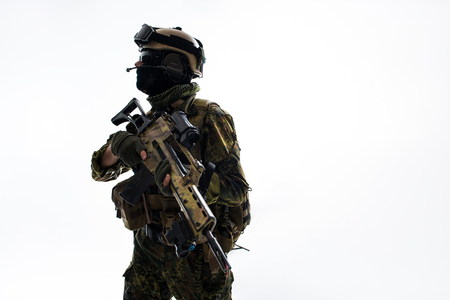 Side view serene defender keeping assault rifle in arms while looking around with concentration. Protection and war concept. Isolated and copy space