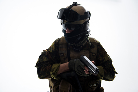 Portrait of stern soldier wearing uniform while holding modern pistol in hands. Military concept. Isolated Stock Photo