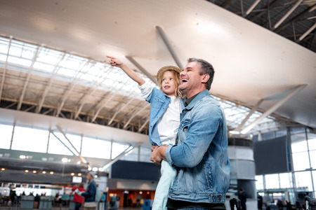 Getting to know world better. Low angle side view of curious little daughter is pointing out to something interesting and asking her cheerful father questions while standing at international airport Foto de archivo
