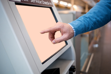 Confirm flight details. Close-up of male hands is using self-service check-in kiosk while standing at international airport building. He is registering on his airplane