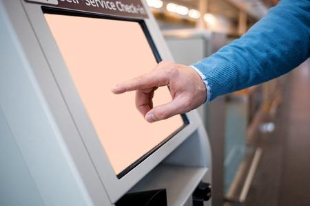 Confirme os detalhes do voo. O close-up das mãos masculinas está usando o quiosque do registro do autosserviço ao estar no edifício do aeroporto internacional. Ele está se registrando em seu avião