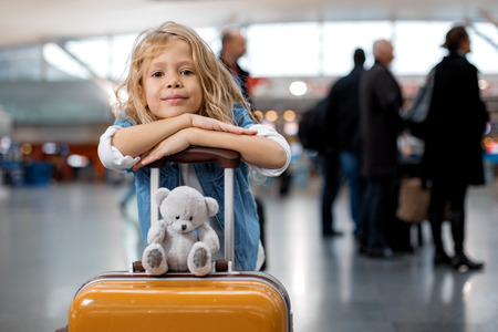 Travel with friend. Portrait of joyful stylish female child is leaning on handle of suitcase with toy bear at airport lounge. She is looking at camera with joy. Copy space with people in background