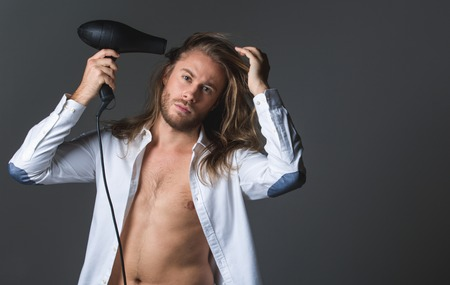 Waist up portrait of calm man holding hairdryer and looking at camera. His shirt is unbuttoned. Copy space in right side. Isolated on grey background