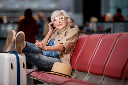 楽しい会話。メガネをかけた白髪の女性の全長の肖像画は、スーツケースに足を乗せながら空港ラウンジの座席に座っている。彼女は笑顔で携帯電