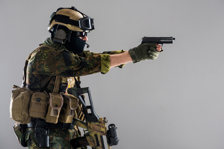 Side view serious soldier firing pistol while wearing helmet and balaclava. Occupation concept. Isolated Stock Photo