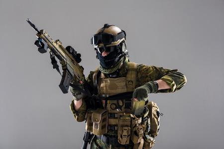폭행 소총을 손에 유지하면서 제복을 입고 심각한 군인의 초상화. 육군 개념입니다. 외딴 스톡 콘텐츠