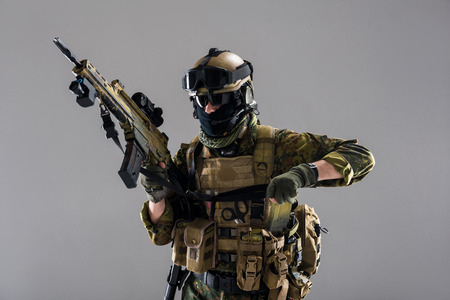 Portrait of severe soldier wearing uniform while keeping assault rifle in hand. Army concept. Isolated 免版税图像