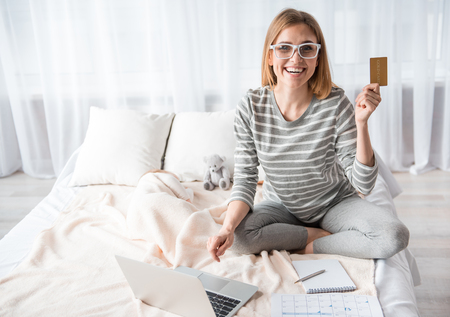 Portrait of positive young female in bedroom with notebook, she is holding plastic card and laughing