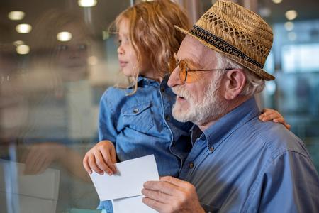 一緒に面白い気持ちの良い祖父のサイドビュープロファイルは、彼の孫娘を手に保持しています。彼らは空港の建物に立ち、好奇心を持って脇に見ながらチケットを維持しています 写真素材 - 92592379