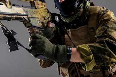 武器から取り外し可能な雑誌を取る男性の腕をクローズアップ。軍事概念