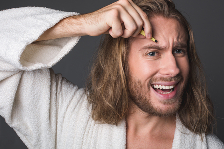 Portrait of discontented longhaired bachelor using tweezers for eyebrows, his face expressing pain. Isolated on grey background
