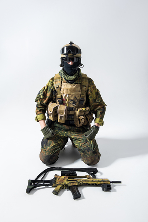 Portrait of serene soldier situating near assault rifle. Military concept