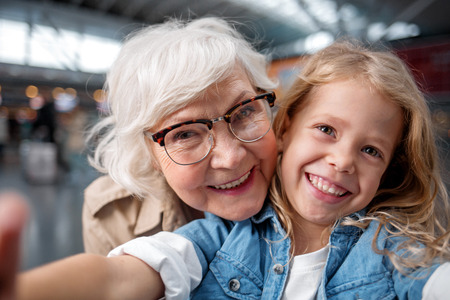 Cool picture. Close-up portrait of joyful happy elderly grandmother is taking selfie with her adorable granddaughter. They are looking at camera with wide smile while standing at airport hall