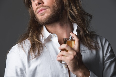 Find your scent. Close up of bearded guy spraying perfume on his neck. Isolated on grey background Stock Photo