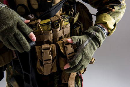 Close up male hands in military uniform holding modern weapon in body armour. Ammunition concept