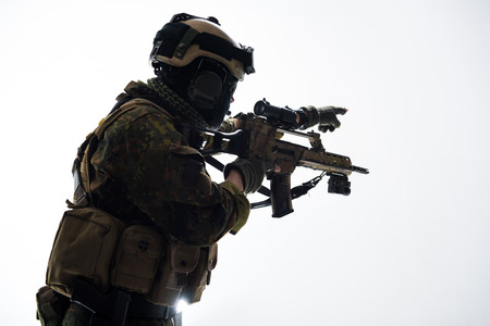 Side view soldier shooting with modern weapon while pointing by hands. War concept. Isolated and copy space Stock Photo