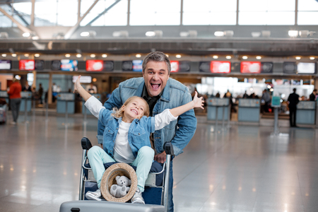 Happy life. Portrait of joyful mature man is pushing airport trolley with suitcases and his nice little daughter who is sitting on it while rising her hands up. Male is looking at camera with joy