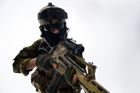 Portrait of serious defender in helmet and balaclava keeping assault rifle. War concept. Isolated Stock Photo