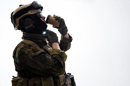 맛있는 커피의 낯 짝을 마시는 군사 옷 측면보기 고요한 군인. 휴식과 군대 개념. 공간 복사 스톡 콘텐츠